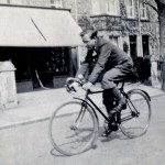 Roger Harding riding past his fathers shop - 1930's